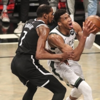 Bucks forward Giannis Antetokounmpo (right) drives past Nets forward Kevin Durant in the third quarter of their series-deciding Game 7 on Saturday in New York. | USA TODAY / VIA REUTERS