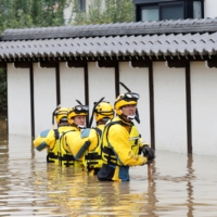 Police search a flooded area in the aftermath of Typhoon Hagibis, which caused severe floods at the Chikuma River in Nagano Prefecture in October 2019.   REUTERS
