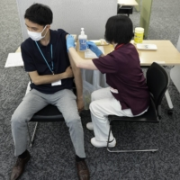 A Suntory Holdings employee receives a dose of the Moderna COVID-19 vaccine at the company's office in Tokyo on Monday.   BLOOMBERG