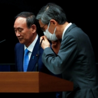 Prime Minister Yoshihide Suga and Shigeru Omi, head of the government's coronavirus advisory panel, leave a news conference at the Prime Minister's Office in Tokyo on Thursday. | POOL / VIA REUTERS
