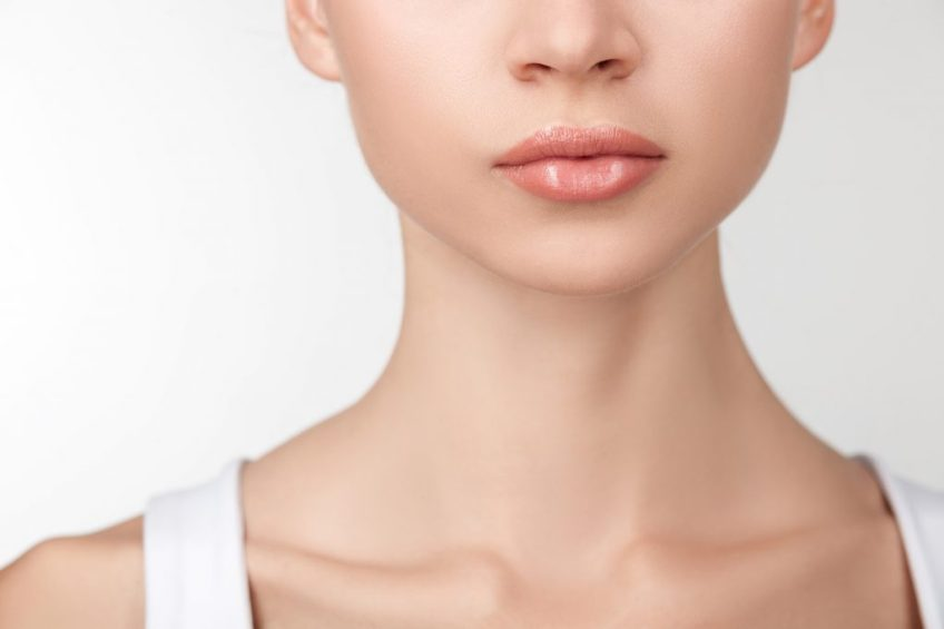 Close up of female neck and half of face. The beautiful woman has perfect skin. Isolated