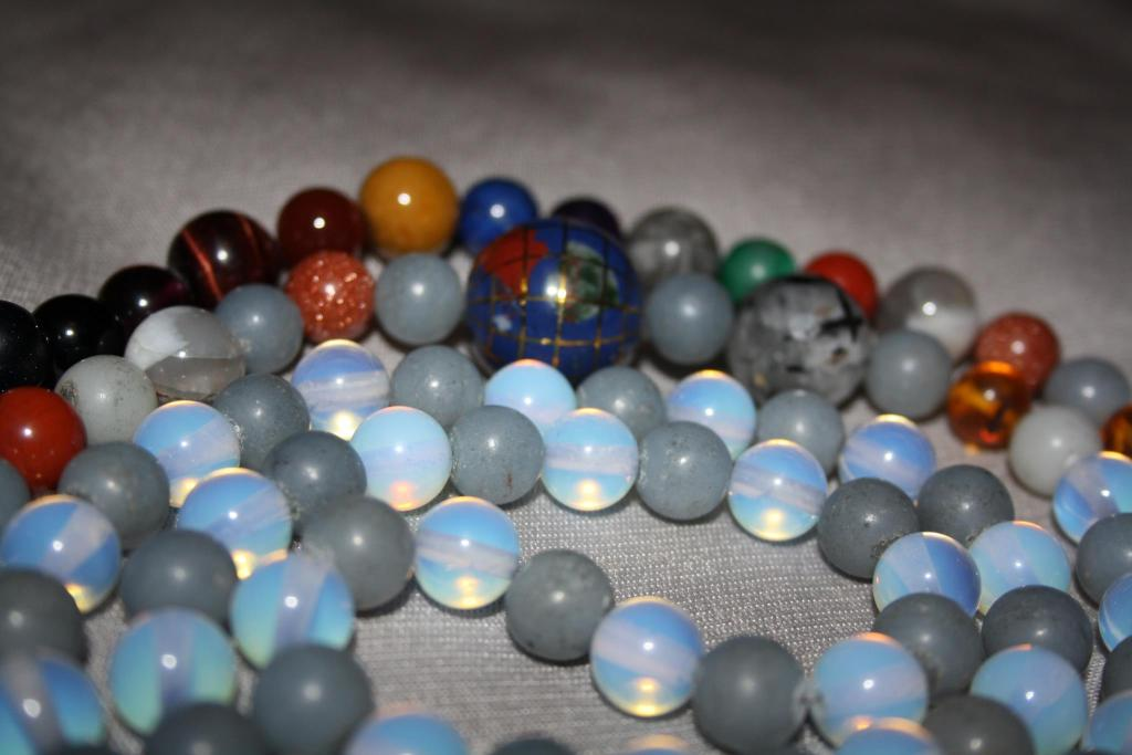 Prayer beads consisting predominantly of pale blue beads and translucent opalescent beads. Feature beads in other colours visible.  Grey background.