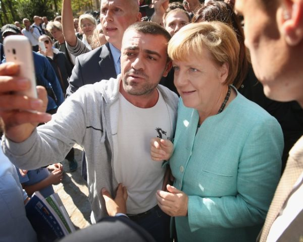 German Chancellor Angela Merkel and immigrant from Middle East