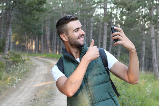 Happy smug man taking selfie and giving himself a thumbs up