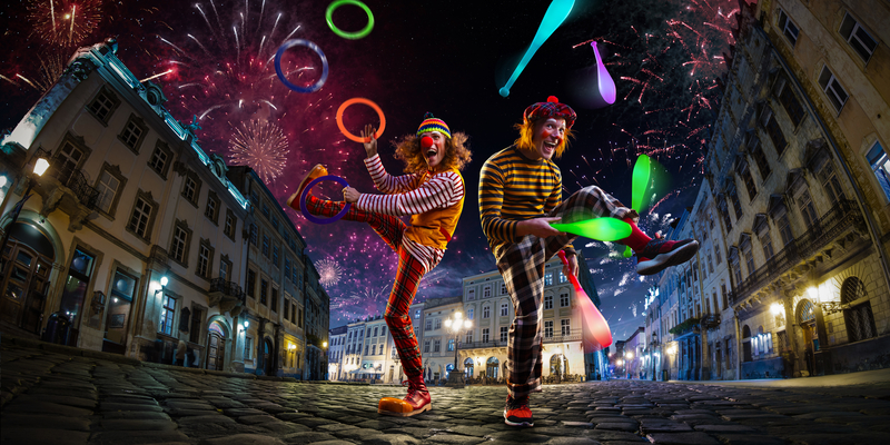 Night street circus performance with two clowns juggling.