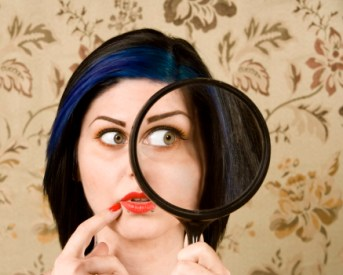 Pretty Woman Holding a magnifying Glass to her Face