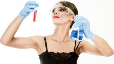 Young woman holding test tubes in hands during scientific experiment.
