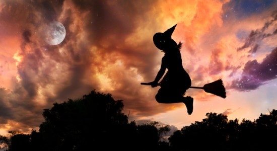 Witch flying on broomstick in the evening.