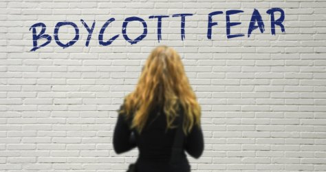 "Blonde woman reads ""boycott fear"" written on the white wall"