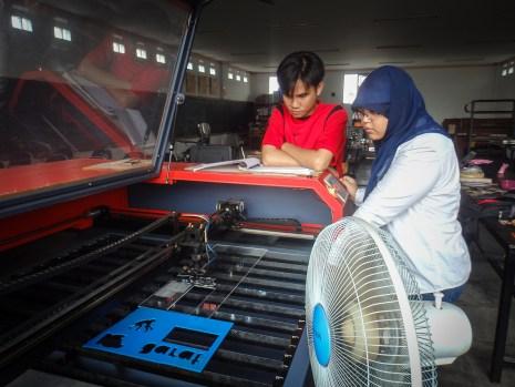 Kang Triyan dan Mbak Fikih dari divisi Operasional sedang membuat gantungan kunci dengan laser cutting