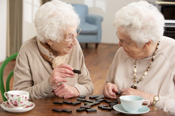 Two older ladies playing dominos and drinking tea