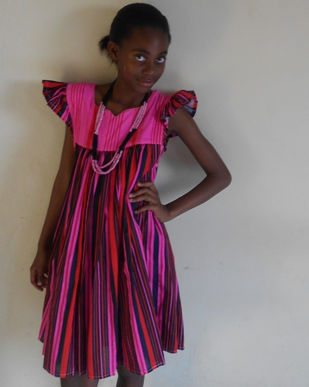 Young Owambo woman in traditional pink dress and beads