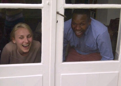 A couple - white female black male look out of a window