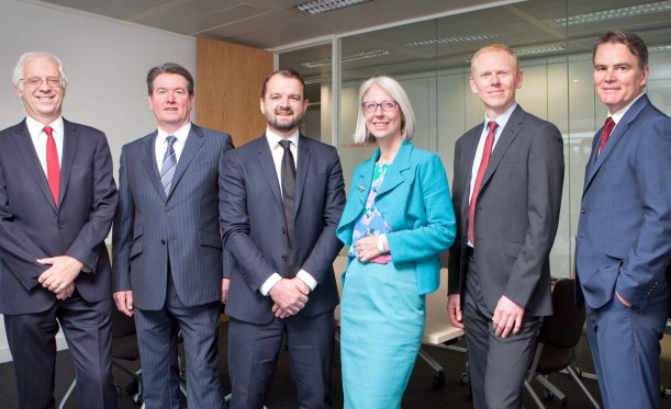 Six senior executives in business wear (one female)