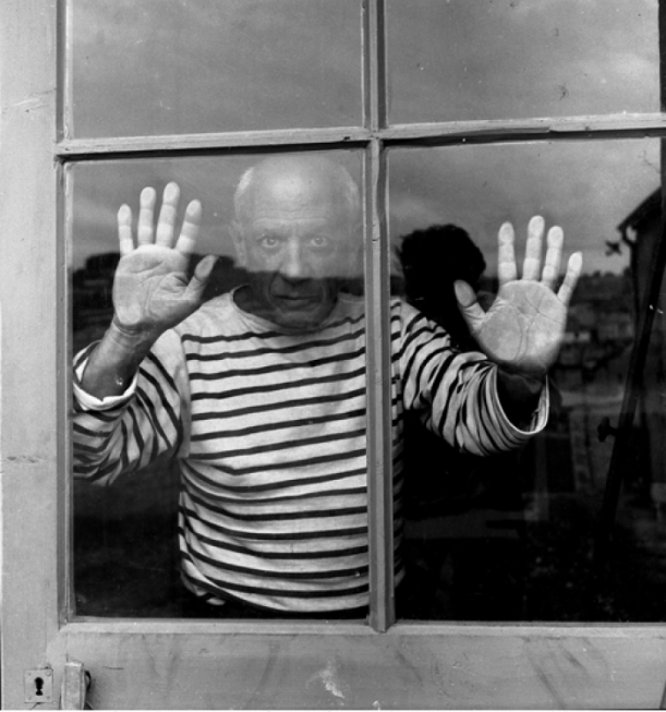 Pablo Picasso in a Breton top with his hands against a window