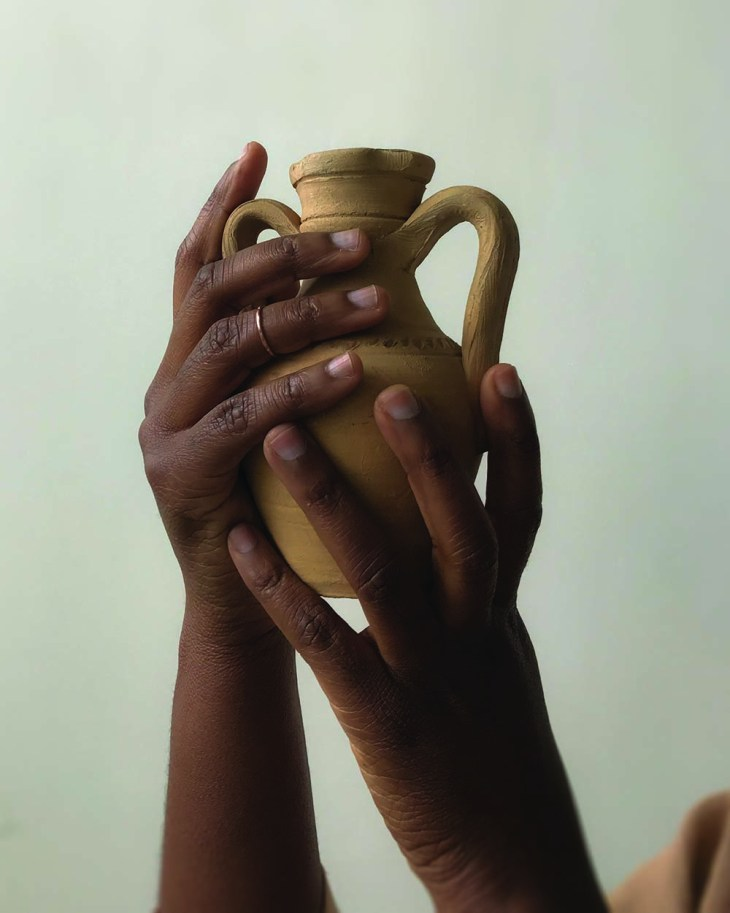Close up of hands holding up a yellow water jug, with focus on dainty gold ring on finger