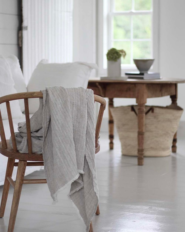 Linen blanket thrown casually over the back of a wooden farmhouse chair
