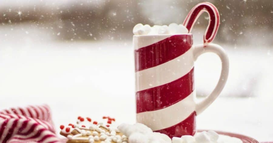Striped mug of hot cocoa with candy cane poking out