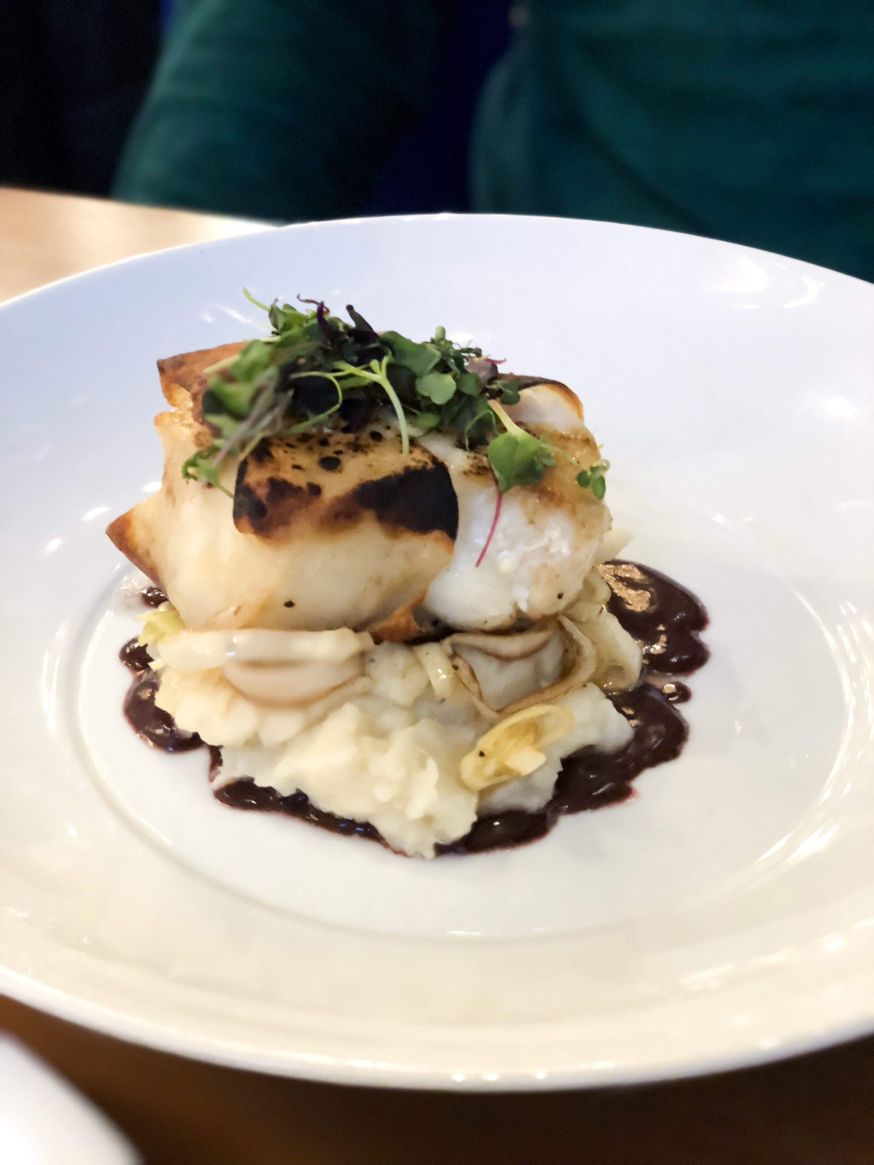 Fresh sea bass served on a bed of mashed potatoes with a red wine reduction