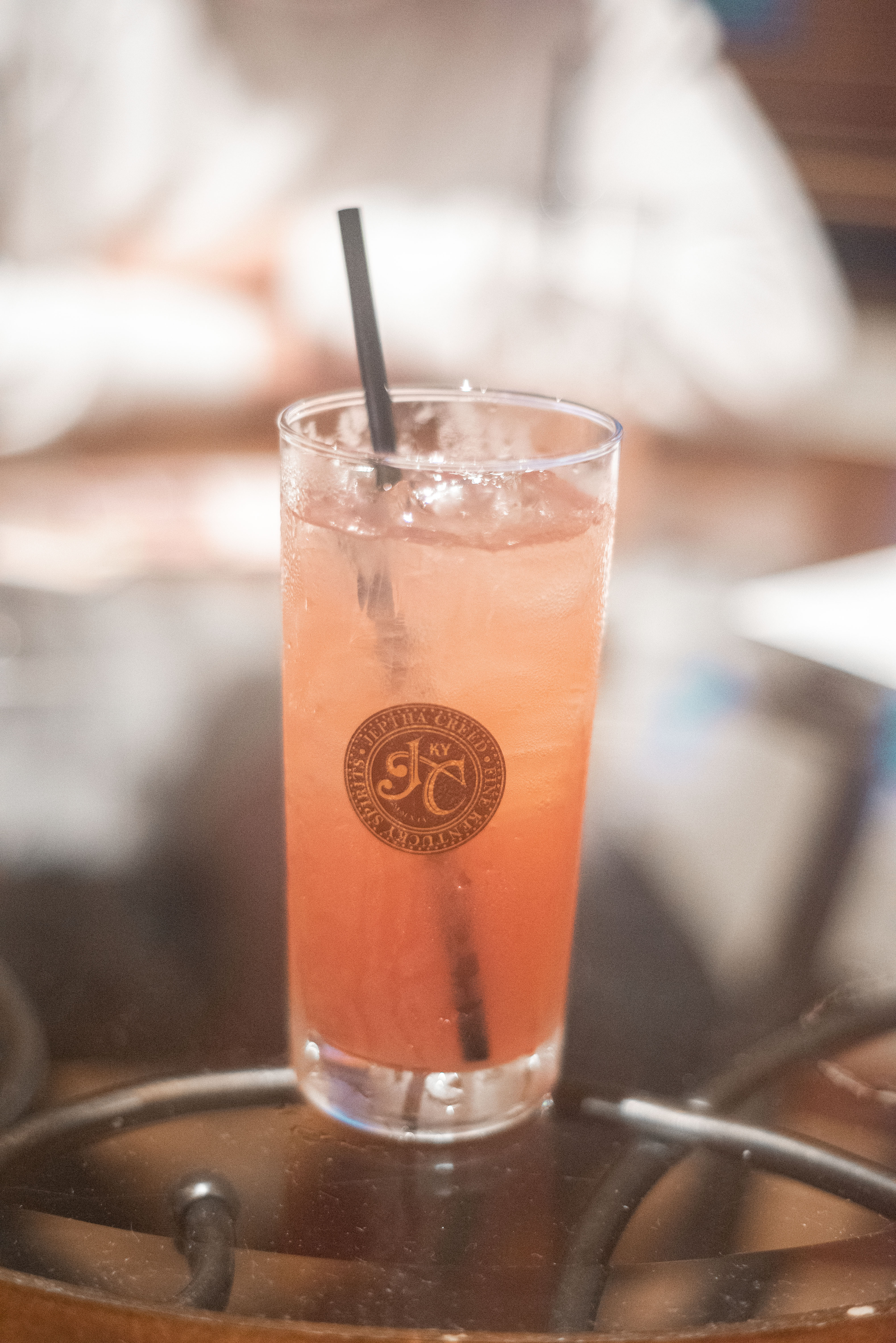Pink cocktail in a tall Jeptha Creed glass with a straw