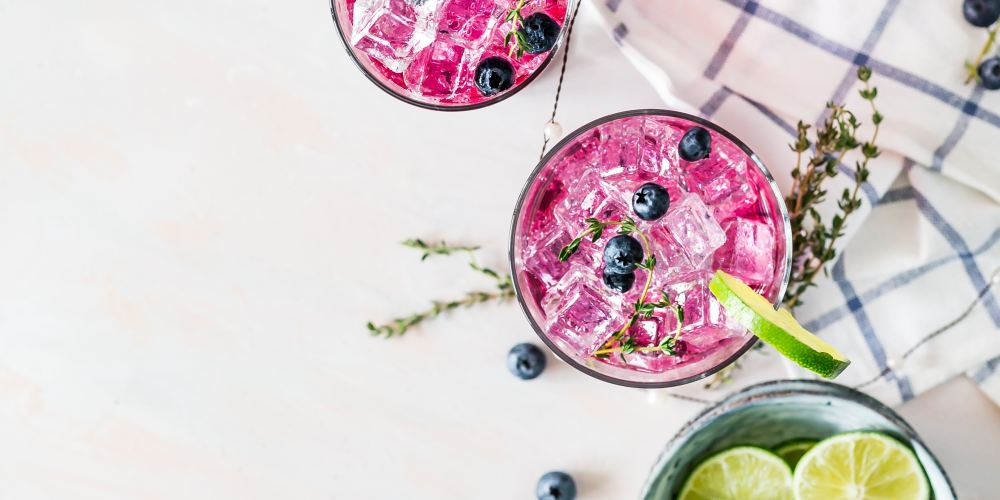 Three pink drinks in glasses with lime and one green drink with in a glass with limes