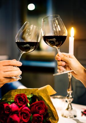 Two wine glasses clinking over a candlelight dinner