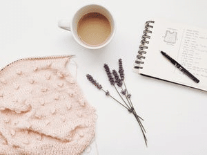 Cup of coffee, pad of paper and heather