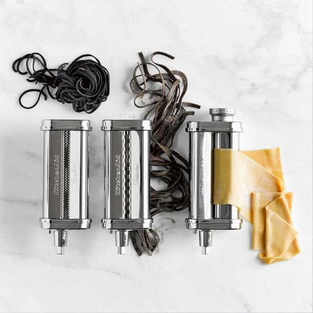 Top-down view of the KitchenAid pasta maker attachments on a marble countertop