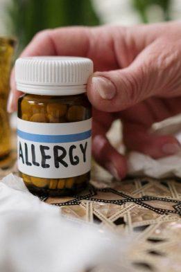 person holding allergy medicine bottle