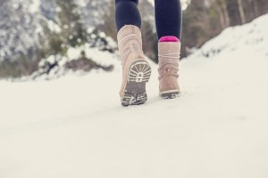 Active woman walking away from the camera through winter snow wearing pale pink boots in the countryside with copyspace in the foreground. Retro filter effect. ** Note: Shallow depth of field