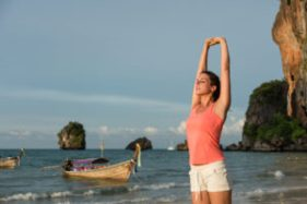 Sporty beautiful woman relaxing and stretching arms and back. Female athlete breathing and doing relaxation exercise at the beach Krabi Thailand.