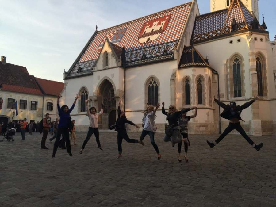 Women Dancing in Plaza in front of European church
