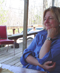 Photo of Carol outside, sitting in the shade by a table - smiling.