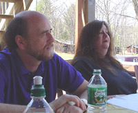Photo of Jim and Melissa outside, sitting at a table - in a conversation.