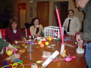 Photo of the group sitting and working around a table with ballons, confetti and other assorted items on it