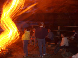"Photo - ""Is it hot out here?"" - Fiery, light distorted, photo of the group sitting around the campfire"