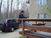 Photo of Jorge sitting on a bench outside, reading something