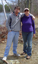 Photo of Judith and Mark standing arm in arm in front of the water