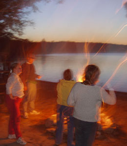 Photo of a fiery evening around the campfire - light from the fire distorted to make everyone seem to be glowing