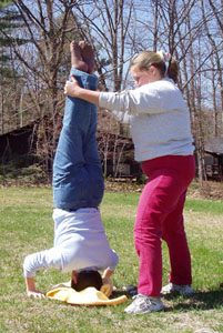 A photo of two participants using teamwork to do a headstand