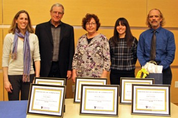 Five Service Learning Faculty Fellows with 6 framed certificates of completion on the table in front of them.
