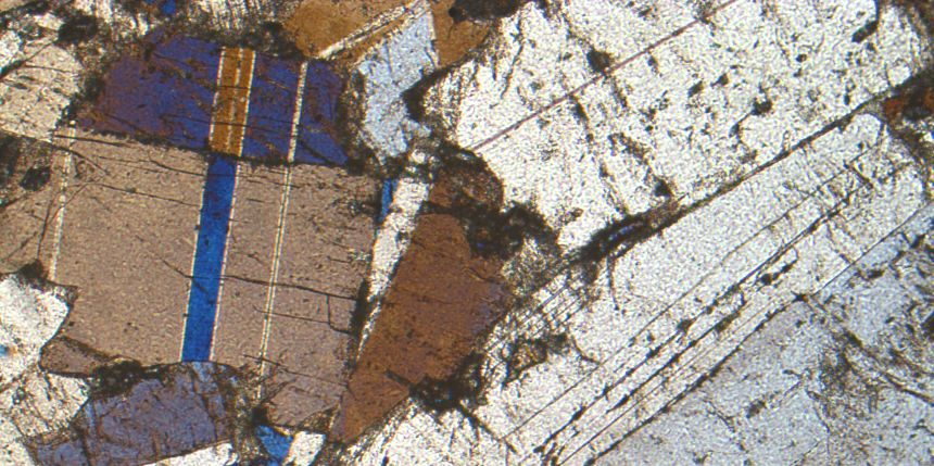 Gray plagioclase , tan and blue pyroxene in thin section, cross-polarized light.