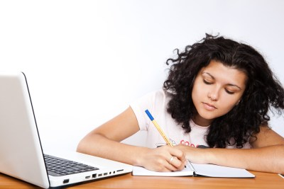 Female college student writing in a note book next to an open laptop