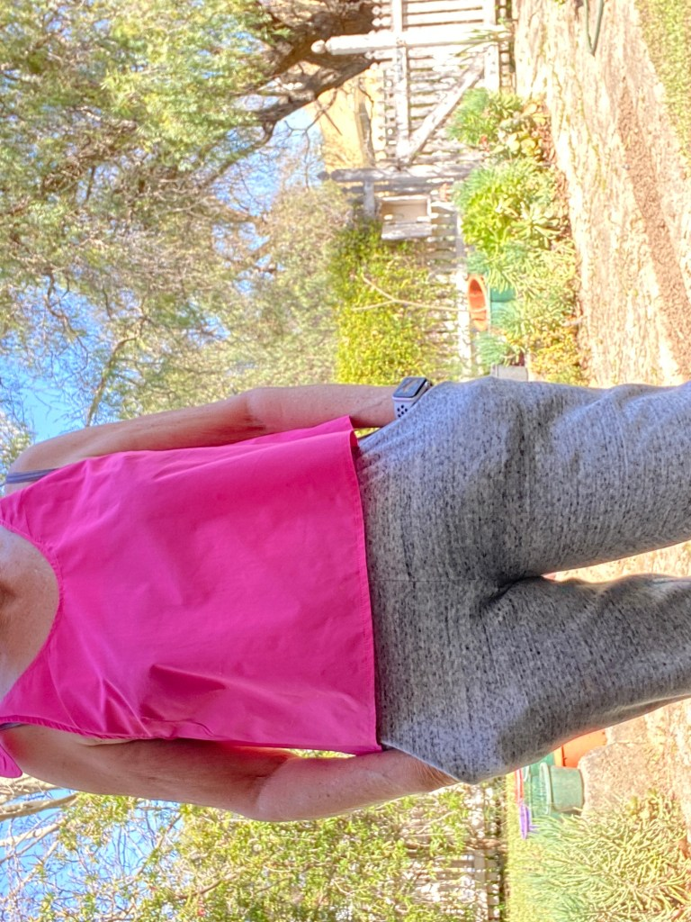 woman with hands in her pockets showing pink tank top.
