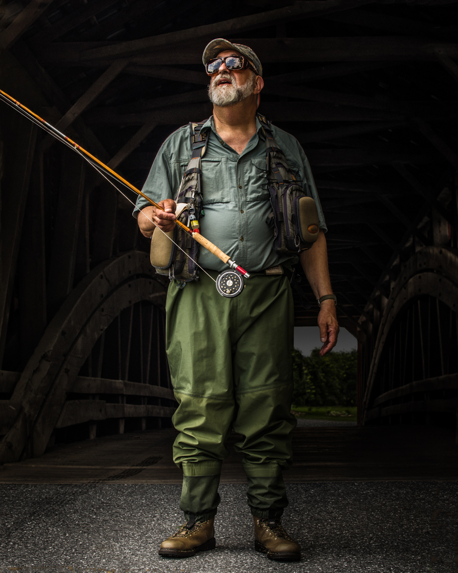 fisherman in front of covered bridge