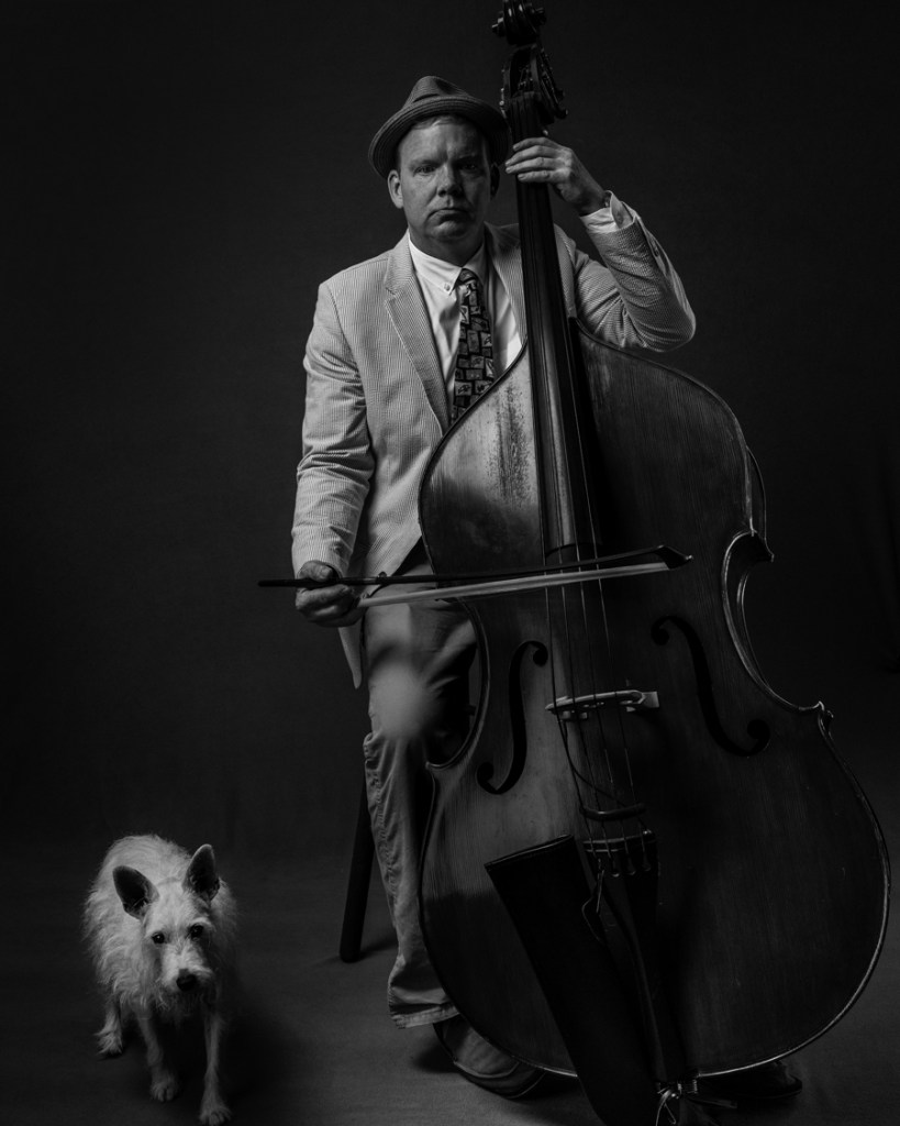 musician with bass and dog