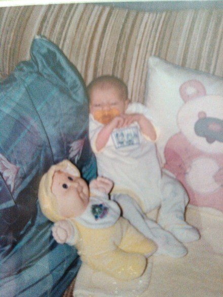 Itty bitty baby me, I am almost the same size as my doll. I was even doing raptor hands as a baby.