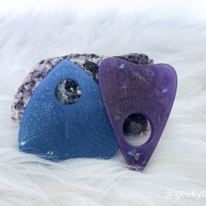 Two Planchettes leaning up against a crystal. One is blue, and other purple