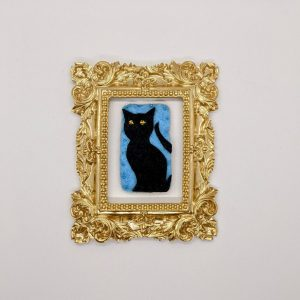 black cat with yellow eyes on blue background inside gold frame