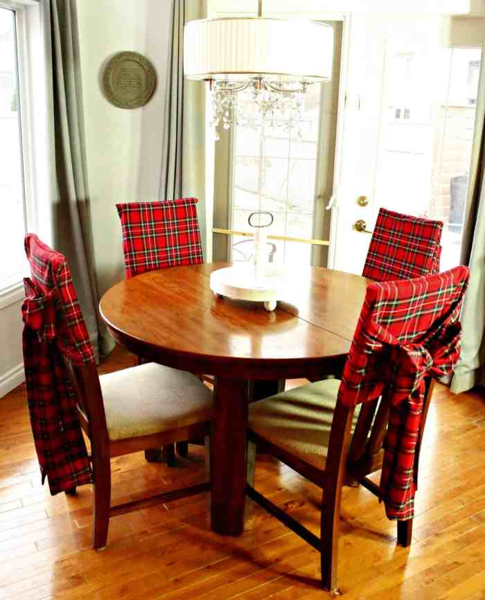 A table for Christmas with four chair covers in red tartan with sashes and bows.